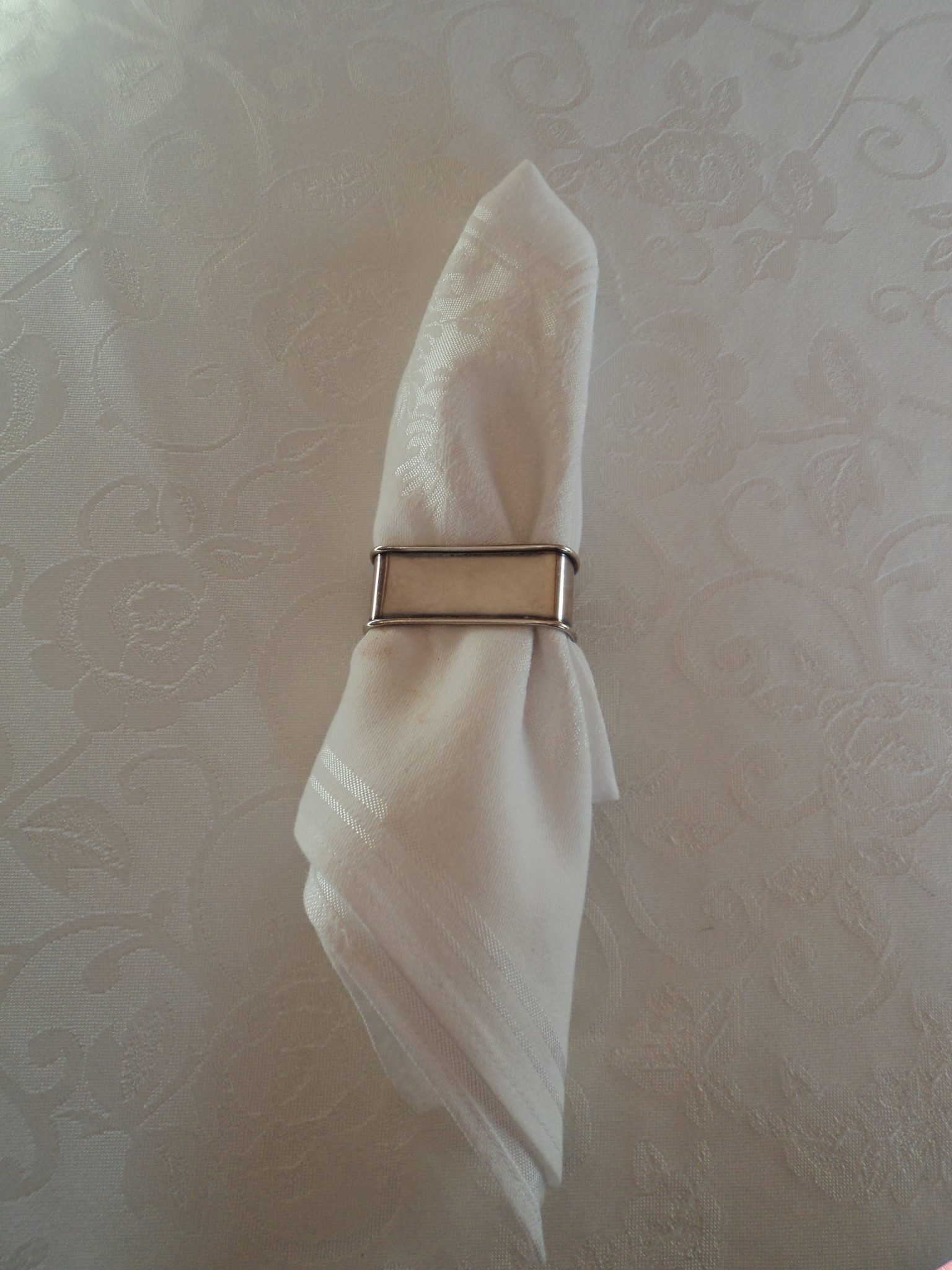 White damask napkin pulled through a silver napkin ring