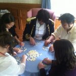 five guests in Regency period dress playing a word game around a table